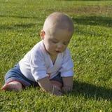 Na trawy bawić się dziecka obsiadanie Zdjęcia Stock