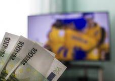 Na TV przedstawienia hokeju w rękach pieniędzy euro, Ups, bukmachery obrazy stock
