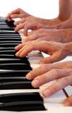 Na uroczystym pianinie sześć ręk Zdjęcia Stock