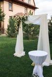 Na wolnym powietrzu dekorujący teren dla ślubnej ceremonii z drewnianym łukiem dekorował z świeżymi kwiatami i beżowym materiałem Zdjęcie Stock