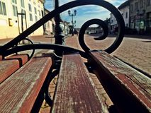 A wooden bench in the center of a cute little town in serbia. Na wooden bench in the center of a cute little town in serbia. market and buildings. irig serbia stock photography