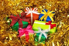 Na złocistym świecidełku pięć kolorowych prezentów. (horyzontalny) Obraz Stock