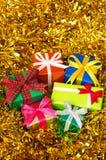 Na złocistym świecidełku pięć kolorowych prezentów. (vertical) Fotografia Stock