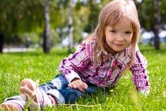 Na zielonej trawie młodej dziewczyny obsiadanie Zdjęcia Stock
