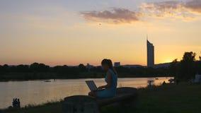 Na zonsonderganghemel en meisje met laptop stock footage