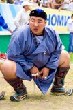 Naadam Festival Heavyweight Wrestler Squatting. Ulaanbaatar, Mongolia - June 11, 2007: Lone large heavyweight wrestler waiting at field level in a squat position Royalty Free Stock Image