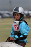 Naadam horse racing. KARKORIN, MONGOLIA, July 8, 2013 : Young boy rides during Naadam. Naadam is a traditional festival where Mongolian wrestling, horse racing Stock Photos