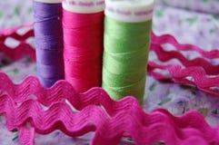 Naai Tijd! Drie kleurrijke spoelen van draad in purple, roze en groen royalty-vrije stock afbeelding