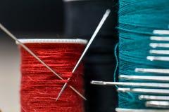 Naaiende draden van verschillende kleuren met partijennaalden Stock Fotografie