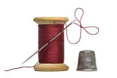 Naaiende dradenspoel met het naaien van geïsoleerde naald en vingerhoedje royalty-vrije stock afbeeldingen