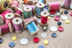 Naaiende hulpmiddelen velen verschillende kleurrijke draad, naald, vele verschillende knopen op houten achtergrond Royalty-vrije Stock Foto