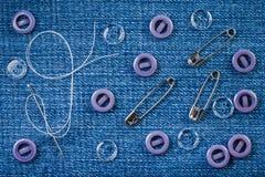Naaiende naald met een witte draad, lilac en transparante knopen en drie spelden op een denimstof stock fotografie
