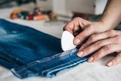Naaister die boord op een paar jeans merken royalty-vrije stock afbeelding