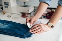 Naaister die boord op een paar jeans merken royalty-vrije stock fotografie