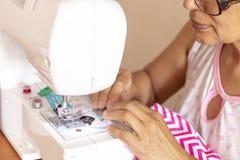 Naaistersvrouw die met haar naaimachine werkt stock foto