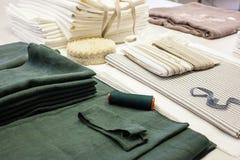 Naaisterswerkplaats in productie met groene en witte die van het linnenstof en kant steekproeven op de lijst worden opgemaakt royalty-vrije stock foto