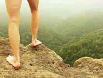 Naakte mannelijke harige benen op piek van rots boven nevelige vallei stock foto's