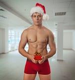 Naakte nog spiermensen die Kerstmiskop dragen die klein rood houden Stock Fotografie