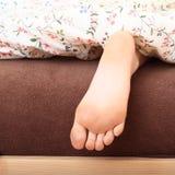 Naakte voet onder deken Stock Afbeelding