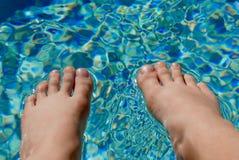 Naakte voeten die op de oppervlakte van poolwater rusten Royalty-vrije Stock Afbeelding