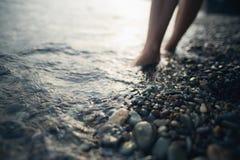 Naakte voeten in het zeewater Stock Afbeelding
