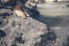 Naakte voeten meisjes die in een stroom van bergrivier lopen Royalty-vrije Stock Afbeelding