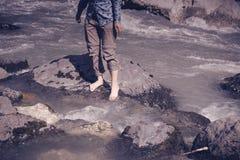 Naakte voeten meisjes die in een stroom van bergrivier lopen Stock Fotografie