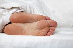 Naakte voeten onder dekbed Stock Foto's