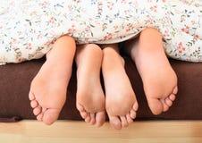 Naakte voeten onder deken Royalty-vrije Stock Foto's