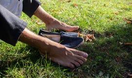 Naakte voeten op het gras met blauwe schoenen stock foto's