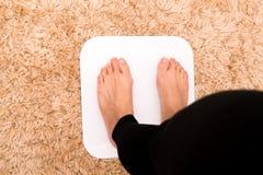 Naakte voeten vrouwen die zich op de gewichtsschalen bevinden Stock Afbeelding