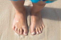 Naakte voeten weinig jong geitjetribune op het strand, hoogste mening Stock Afbeelding