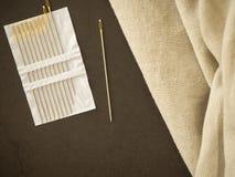 naald en de natuurlijke achtergrond van de linnentextuur stock fotografie
