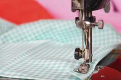 Naald met draad en gekleurde stoffen op een oude naaimachine Retro gestileerde foto Selectieve nadruk Stock Fotografie