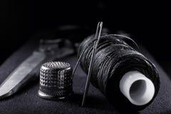Naald met draad, vingerhoedje, spoel met zwarte draad en schaar op zwarte achtergrond Stock Fotografie