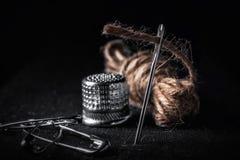Naald met draad, vingerhoedje, spoel met zwarte draad en spelden op zwarte achtergrond Stock Fotografie