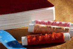 Naald, spoelen met draden, boek en een meetlint Royalty-vrije Stock Fotografie
