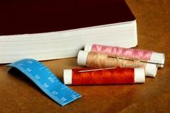 Naald, spoelen met draden, boek en een meetlint Stock Foto's