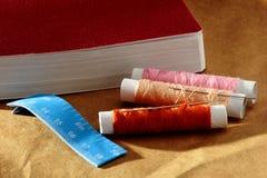 Naald, spoelen met draden, boek en een meetlint Royalty-vrije Stock Afbeeldingen
