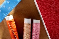Naald, spoelen met draden, boek en een meetlint Stock Afbeeldingen