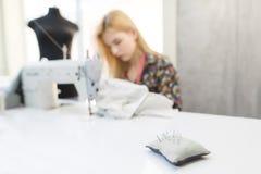 Naalden in een hoofdkussen op de achtergrond van naaisters die aan een naaimachine en een ledenpop werken royalty-vrije stock foto