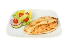 Stuffed naan and salad. Naan bread stuffed with chicken tikka and a salad garnish on a plate isolated against white Royalty Free Stock Images