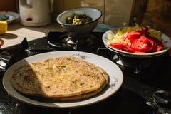 Naan kochte zu Hause auf einer weißen Platte auf einem Gasherd lizenzfreie stockfotografie