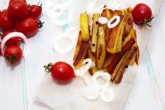 Naar huis gemaakt aardappelvoedsel met tomatenkers en ui op kraftpapier-document royalty-vrije stock afbeeldingen