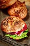 Naar huis gemaakte hamburger op het rustieke weefsel. Broodjes op de achtergrond. Royalty-vrije Stock Fotografie