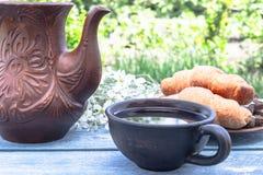 Naast de croissants en de bloemen dichtbij de kruik is een kop thee stock foto's