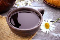 Naast de croissants en de madeliefjes is een kop thee royalty-vrije stock foto
