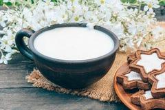 Naast de koekjes en de witte bloemen is een kop van melk op een servet stock afbeelding