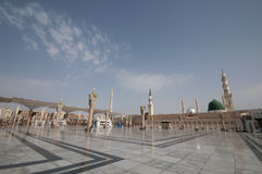 Nabawi Mosque compound in Medina, Saudi Arabia. Pilgrims walk at the Nabawi Mosque compound in Medina, Saudi Arabia. The mosque is the second holiest mosque in royalty free stock images