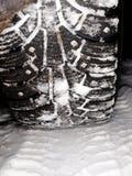 Nabijać ćwiekami zim opony na śniegu Fotografia Stock